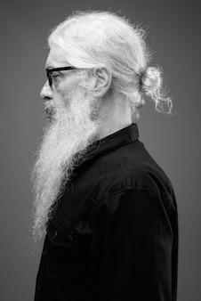 Портрет старшего бородатого мужчины в черной рубашке на сером в черно-белом