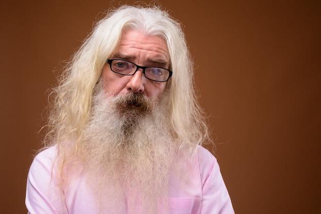 Портрет старшего бородатого мужчины в розовой рубашке