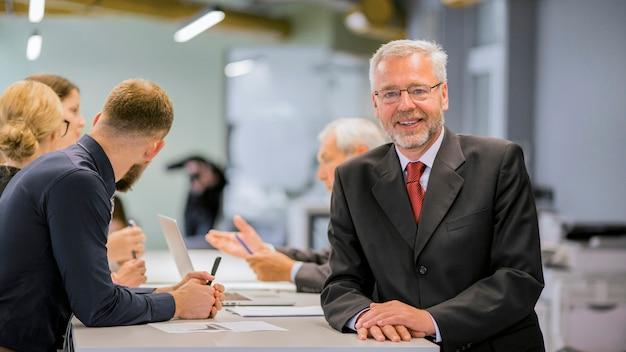 Портрет старшего бизнесмена перед бизнесмены, обсуждение в офисе