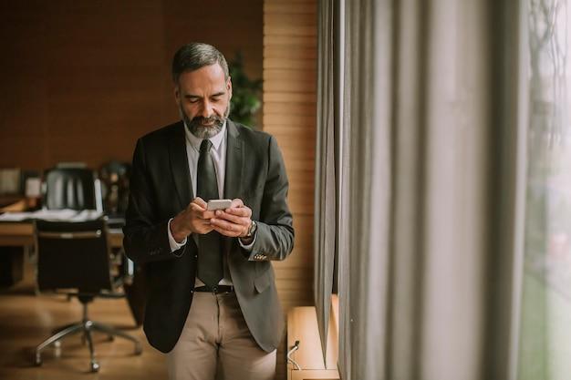 Портрет старшего бизнесмена используя сотовый телефон в современном офисе