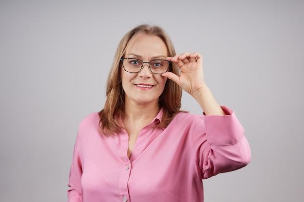 眼鏡をかけているピンクのブラウスのシニア実業家の肖像画