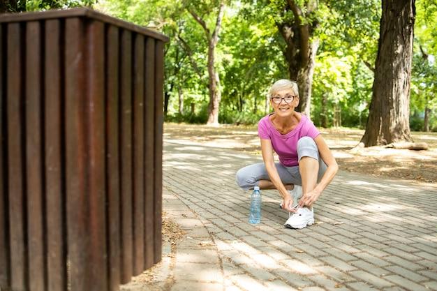 공원에서 조깅하기 전에 신발끈을 묶는 백인 고위 여성의 초상화.