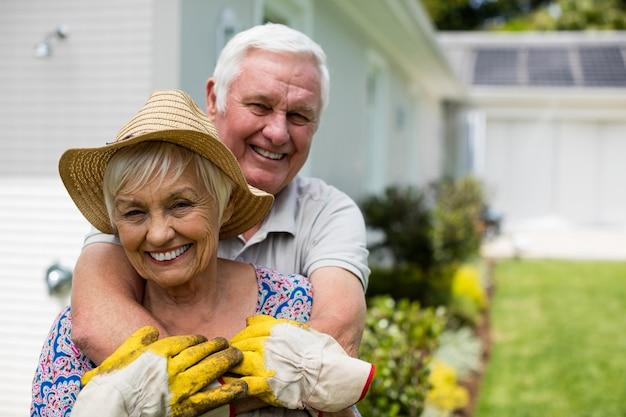 裏庭で抱き合っている年配のカップルの肖像画