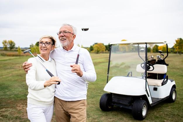 Портрет пожилой пары, наслаждающейся выходом на пенсию, играя в гольф на поле для гольфа.