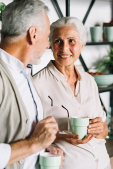 Portrait of senior couple holding cup of coffee looking at each other