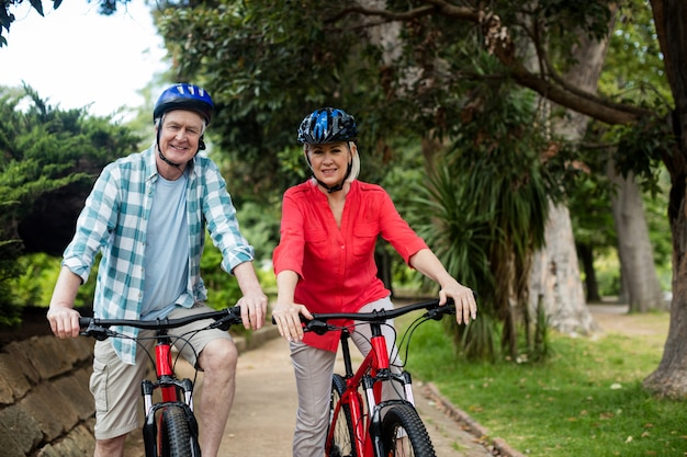 Портрет старших пар стоя с велосипедом в парке