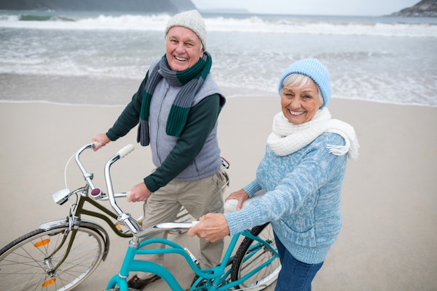 Портрет старших пар, стоя с велосипедами на пляже