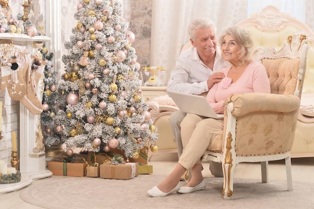 배경에 크리스마스 장식으로 노트북을 사용하는 수석 부부의 초상화