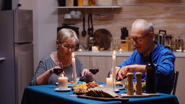 아늑한 주방에 있는 테이블에 앉아 있는 레드 와인 잔을 들고 있는 노부부의 초상화. 행복한 노인 부부는 집에서 함께 식사를 하고 식사를 즐기고 기념일을 축하합니다