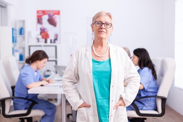Портрет старшего врача, улыбаясь в камеру в конференц-зале больницы с медицинским персоналом в фоновом режиме.