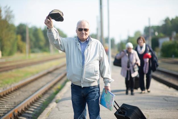 Портрет старшего пожилого мужчины, держащего шляпу и карту, в ожидании поезда в путешествии