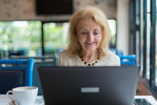 앉아 노트북 컴퓨터를 사용 하여 수석 노인 여성의 초상화