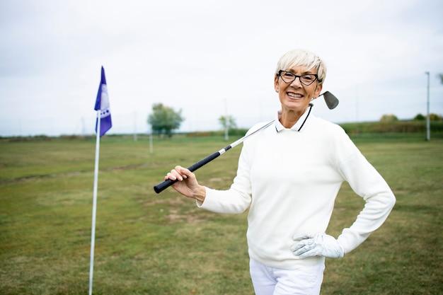 골프를 치며 은퇴를 즐기는 고위 여성 골퍼의 초상화.