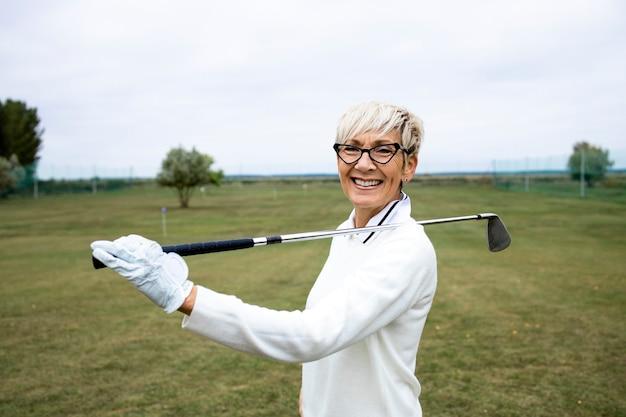 골프 코스에서 골프 클럽을 잡고 웃고 있는 은퇴한 고위 여성 골퍼의 초상화.