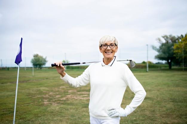 골프 코스에 골프 클럽이 서 있는 수석 여성 골퍼의 초상화.