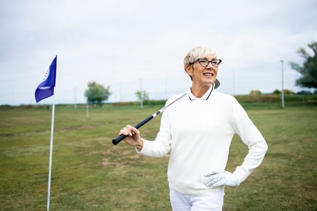 골프 코스에서 골프를 치는 수석 회색 머리 여자의 초상화.