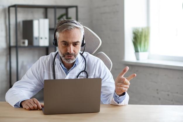 사무실에서 환자와 화상 채팅을 하기 위해 노트북을 사용하는 수석 회색 머리 남성 의사의 초상화. 진단 및 치료 권장 사항에 대한 의사와의 온라인 상담. 원격 의료 개념입니다.