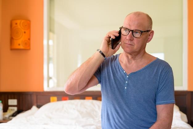 Портрет старшего красивого скандинавского мужчины, расслабляющегося в спальне