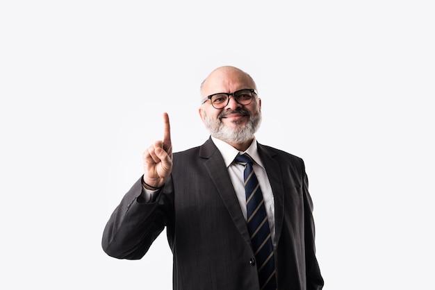 白い背景に対して孤立して立って、指を使用して数字の兆候を示すインドのアジアのシニアビジネスマンの肖像画