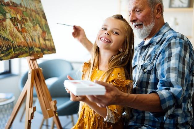 Портрет старшего мужчины, дедушка учит детей рисованию. счастливое семейное время