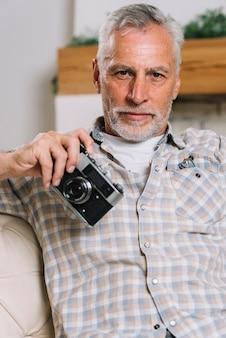 Портрет старшего человека, держащего камеру в руке, глядя на камеру