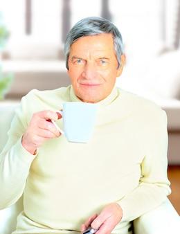 Портрет старшего мужчины, держащего кружку кофе, улыбаясь в камеру