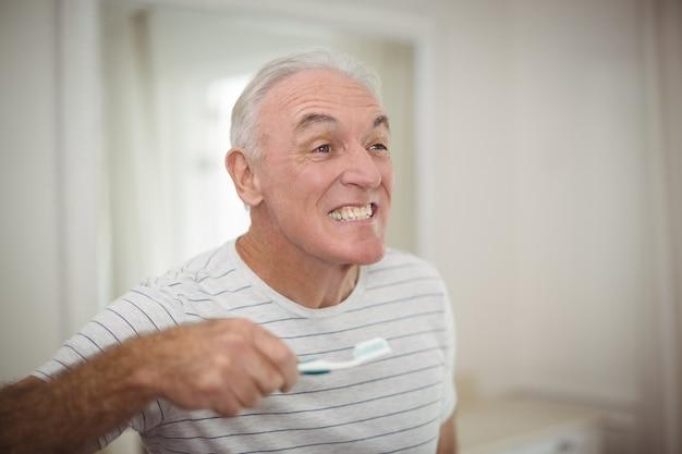 バスルームに歯ブラシを保持している年配の男性人の肖像画