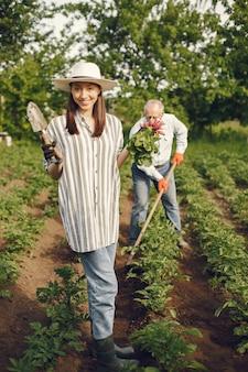 Портрет старшего мужчины в шляпе садоводства с внучкой