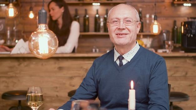 カメラに微笑んでレストランで年配の男性の肖像画。 60代の男性。幸せな老人。
