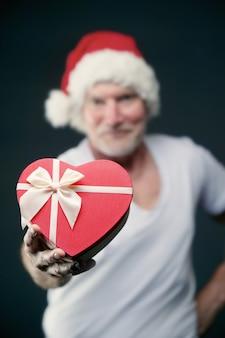 彼の手に贈り物を保持しているジムのサンタクロース帽子の年配の男性の肖像画クリスマスのコンセプト