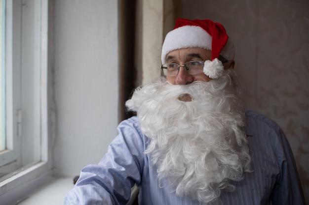 Портрет старшего мужчины в новогодней шапке, смотрящего в камеру
