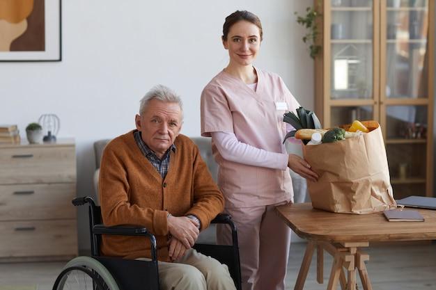 카메라를 보고 있는 젊은 여성 간병인과 식료품 가방을 들고 포즈를 취한 휠체어를 탄 노인 초상화, 공간 복사