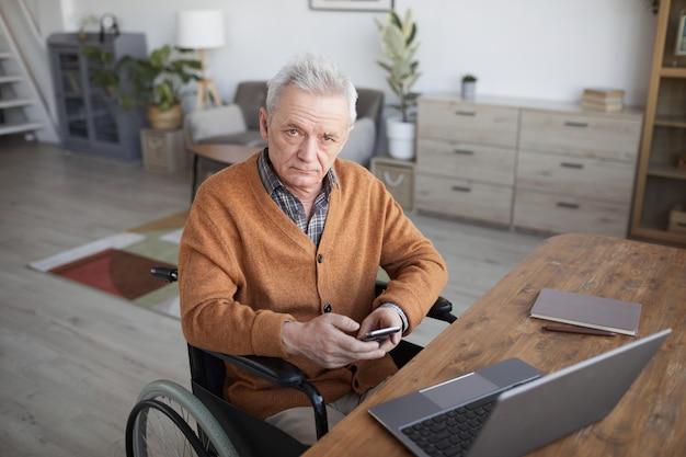 家のインテリアの机で作業し、カメラを見ながらスマートフォンを使用して車椅子の年配の男性の肖像画