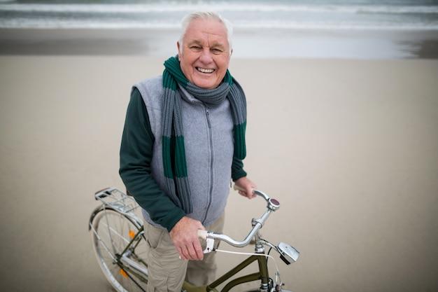 Портрет старшего мужчины езда на велосипеде на пляже