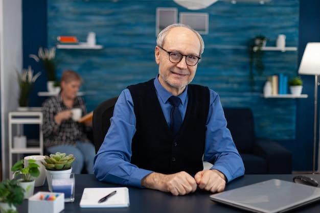 Портрет старшего мужчины, сидящего за столом в офисе