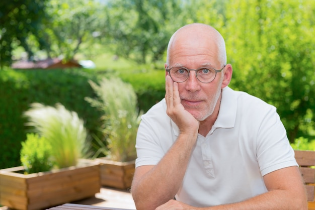 Портрет старшего человека, улыбаясь в саду