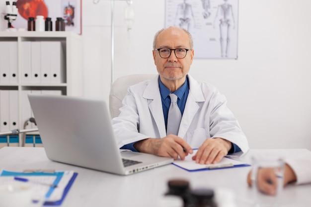 의료 전문 분야에서 일하는 회의실 책상에 앉아 카메라를 들여다보는 노인 전문 의사의 초상화. 클립보드에 약을 처방하는 의사