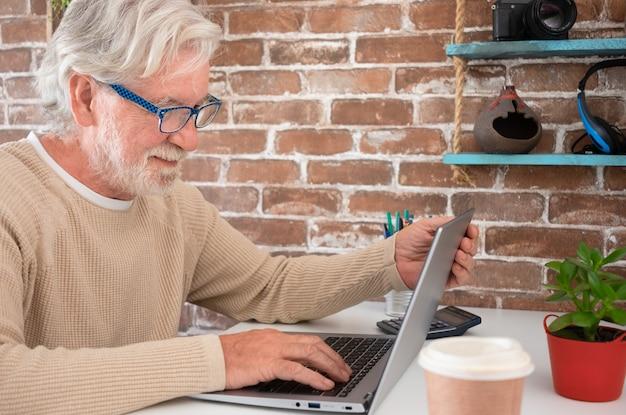 Портрет старшего человека с помощью портативного компьютера дома улыбается. кирпичная стена на фоне