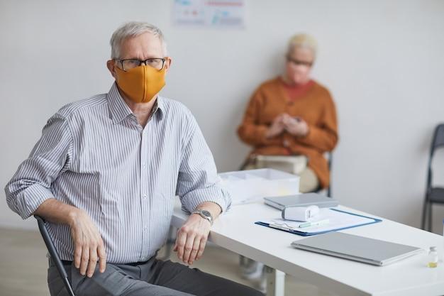 Портрет старшего мужчины в маске и смотрящего в камеру, сидя за столом в офисе врачей, копией пространства