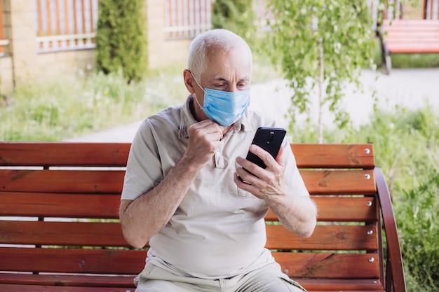 携帯電話で医療マスクを着ている年配の男性の肖像画。コロナウイルスの概念。呼吸保護