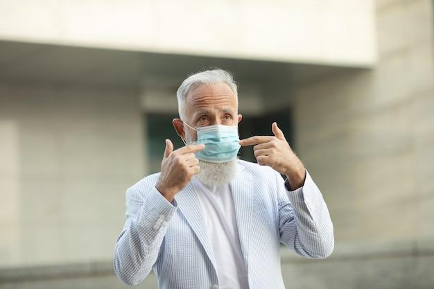 의료 마스크를 쓰고 수석 남자의 초상화