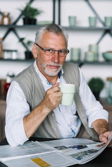 Portrait of senior man with coffee cup in his hand reading newspaper