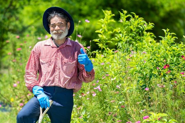 屋外の庭で働いている園芸工具を持つ年配の男性の肖像画。