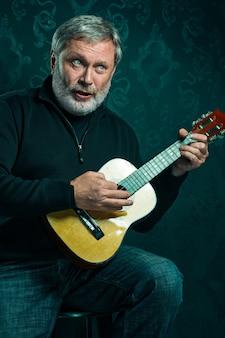 ギターを持つ年配の男性の肖像画。
