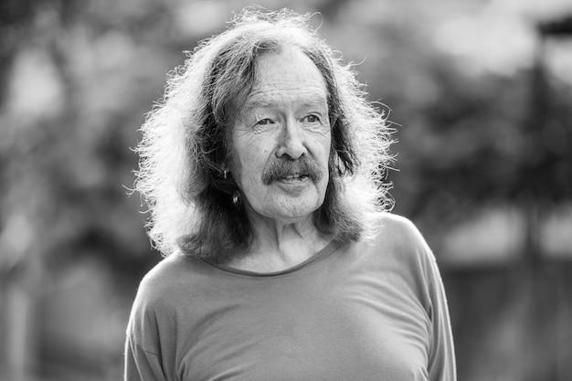 Портрет старшего мужчины с усами на улице на открытом воздухе в черно-белом