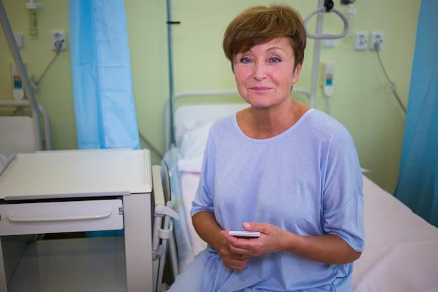 Портрет старшего пациента, сидя на кровати