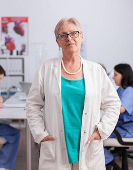 会議室で働くカメラの前に立っている年配の小児科医の女性の肖像画。病気の治療を分析する医学的専門知識を提示する聴診器を持つ心臓専門医