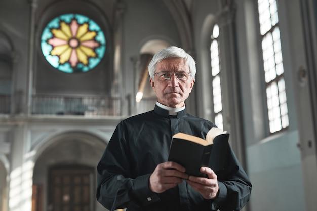 教会に立っている間、聖書を持ってカメラを見ている先輩司祭の肖像画
