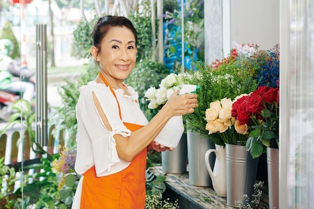 店内の花に水をまくオレンジ色のエプロンでシニアベトナムの花屋の肖像画
