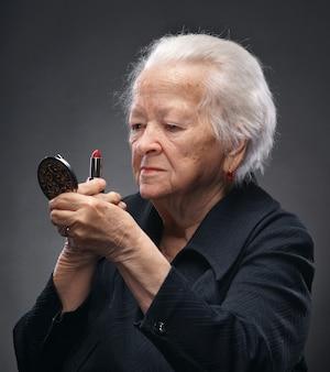 립스틱을 적용하는 고위 여자의 초상화입니다. 어두운 배경에 스튜디오에서 포즈
